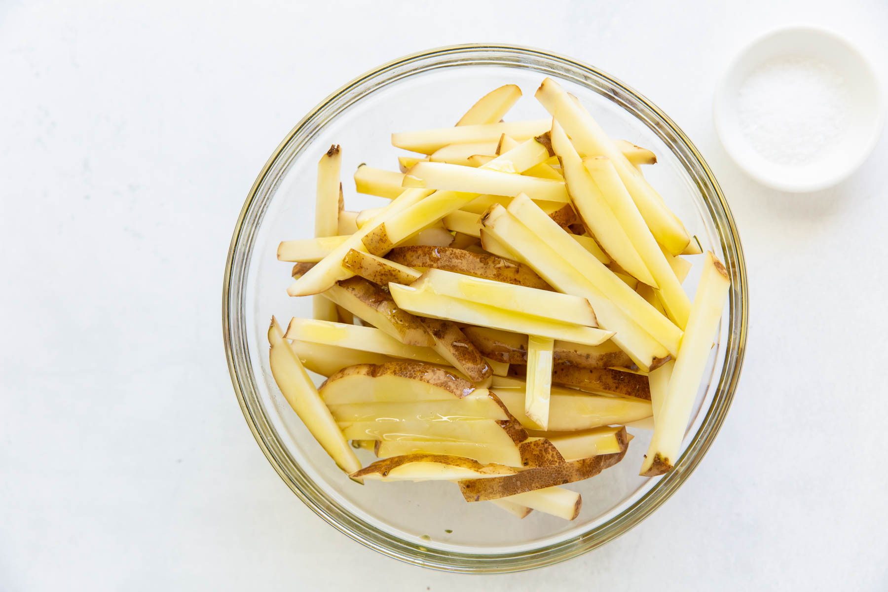 french fries in a glass bowl drizzled with olive oil