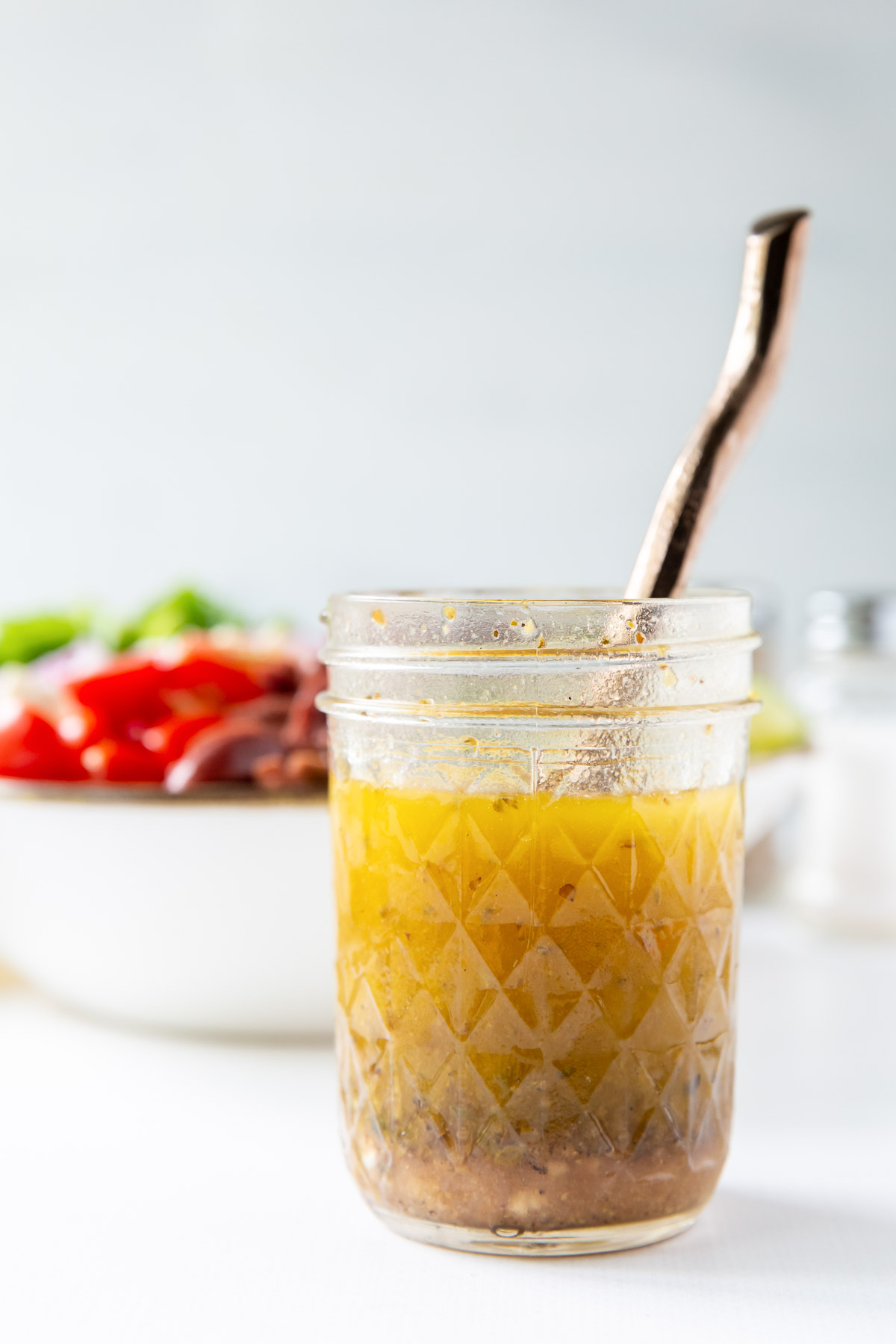 greek salad dressing in a mason jar with a spoon with greek salad in background