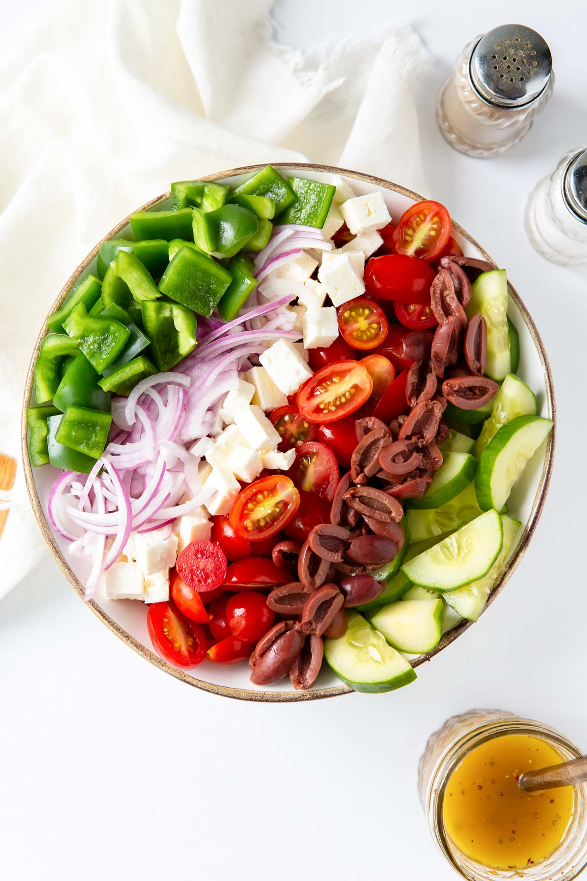 bell pepper, red onion, feta cheese, tomatoes, kalamata olives and cucumber arranged in rows in a large bowl