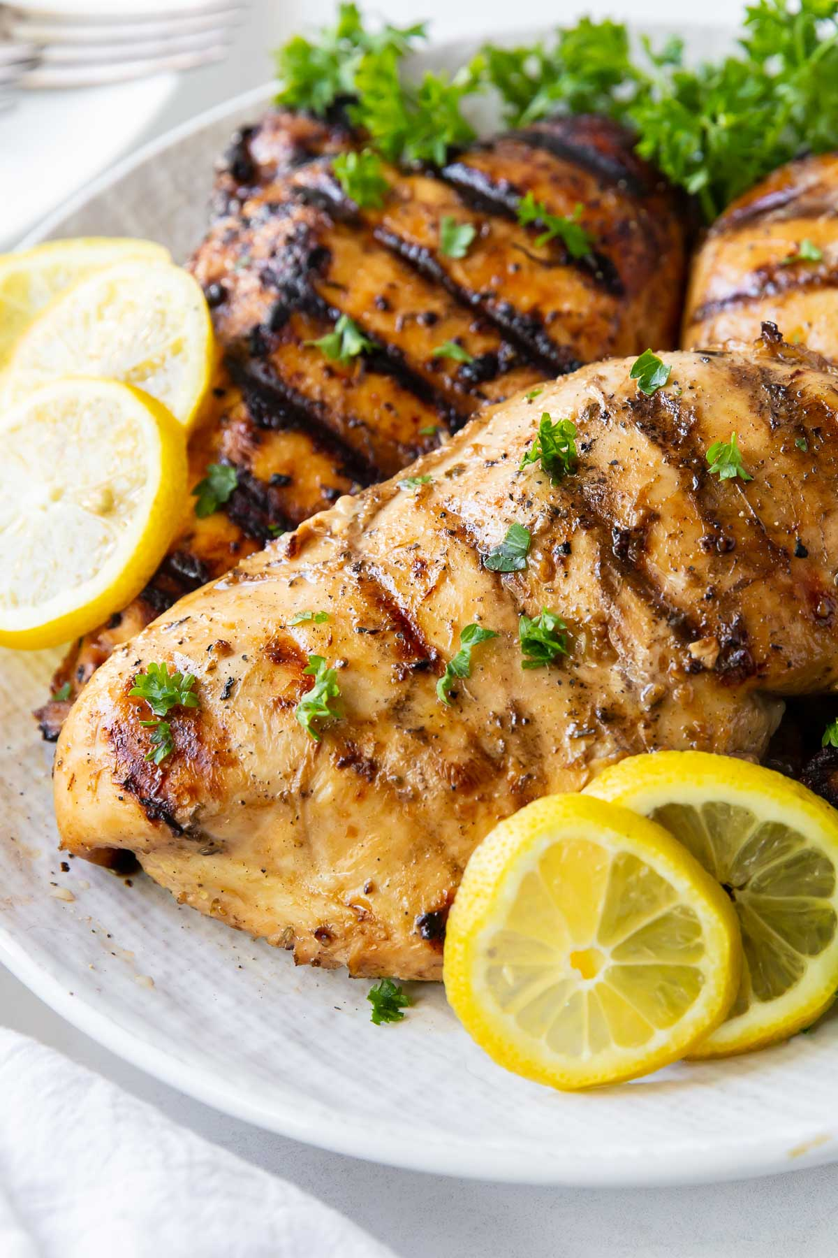 close up of grilled marinated chicken breasts on a plate garnished with parsley and lemon slices