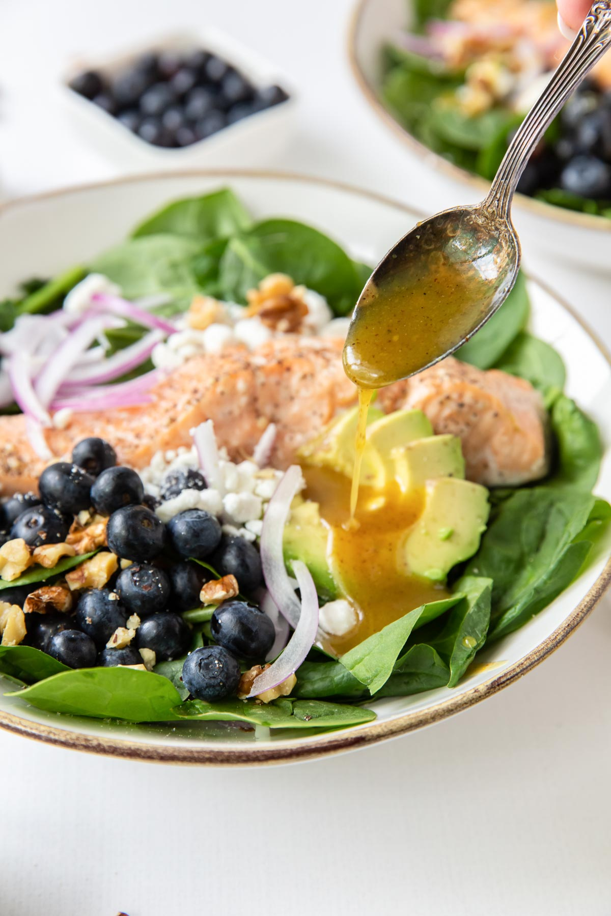 drizzling honey mustard dressing onto a spinach salad with avocado and salmon.