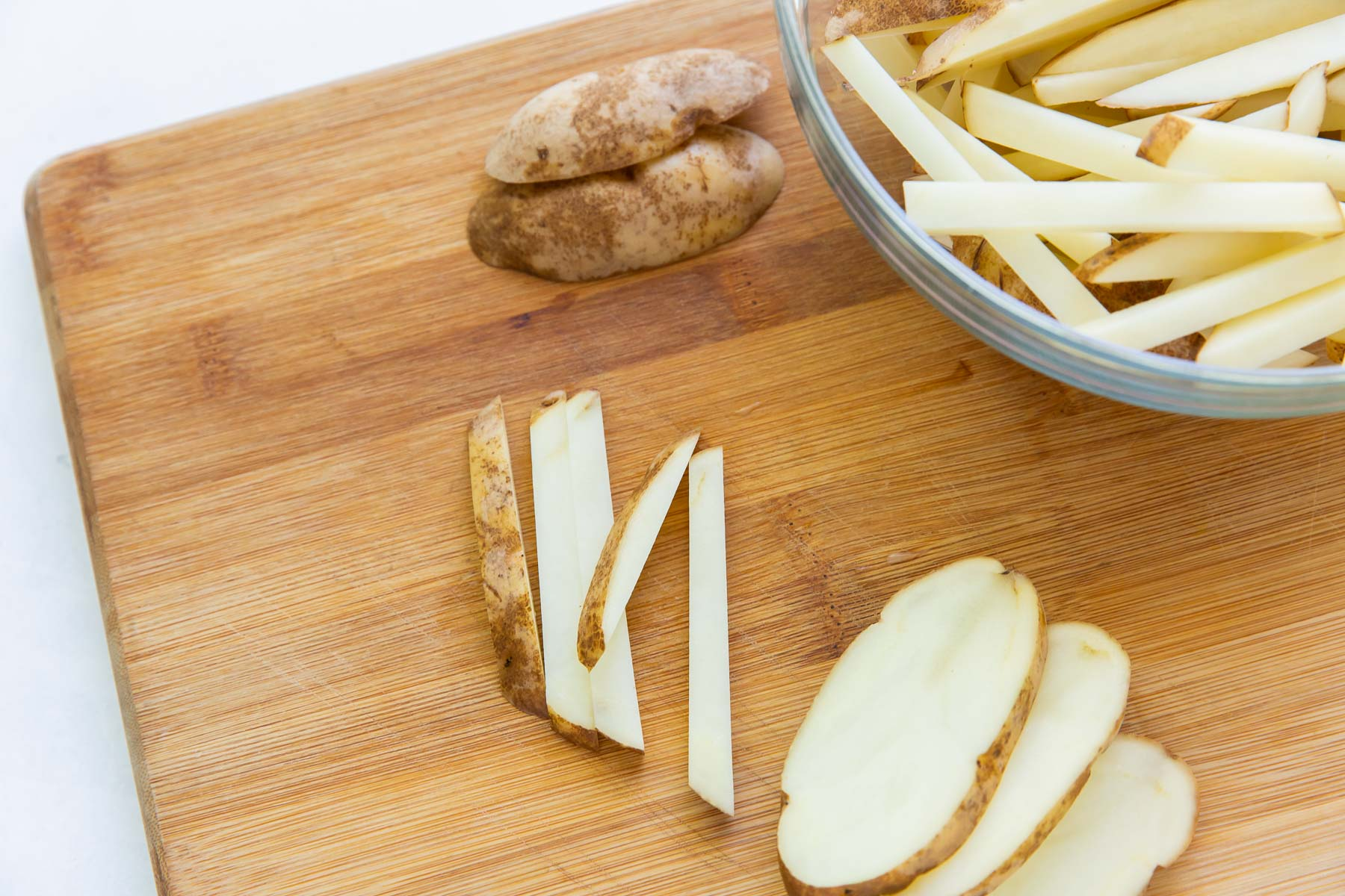 cutting a potato into 1/4-inch thick sticks