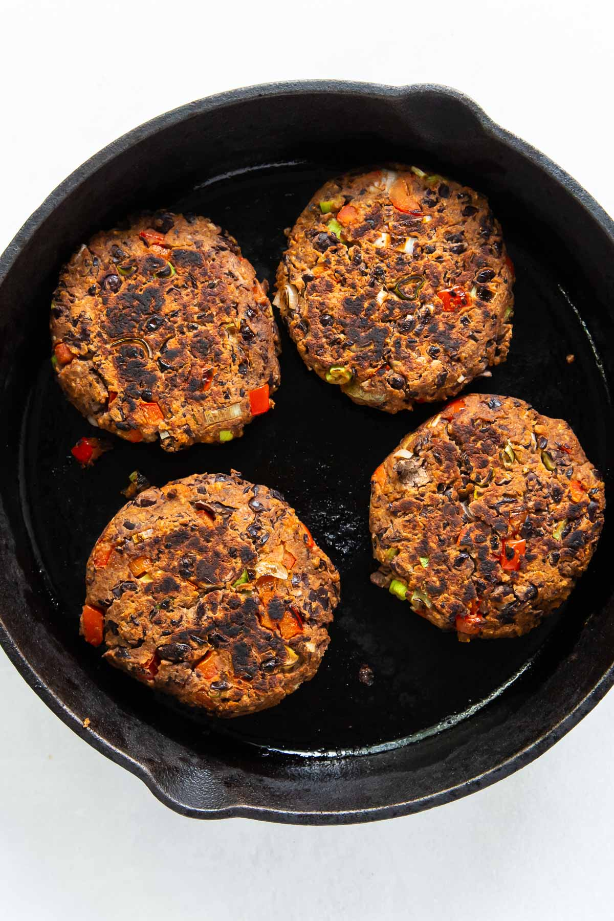 four browned black bean burgers in a cast iron skillet