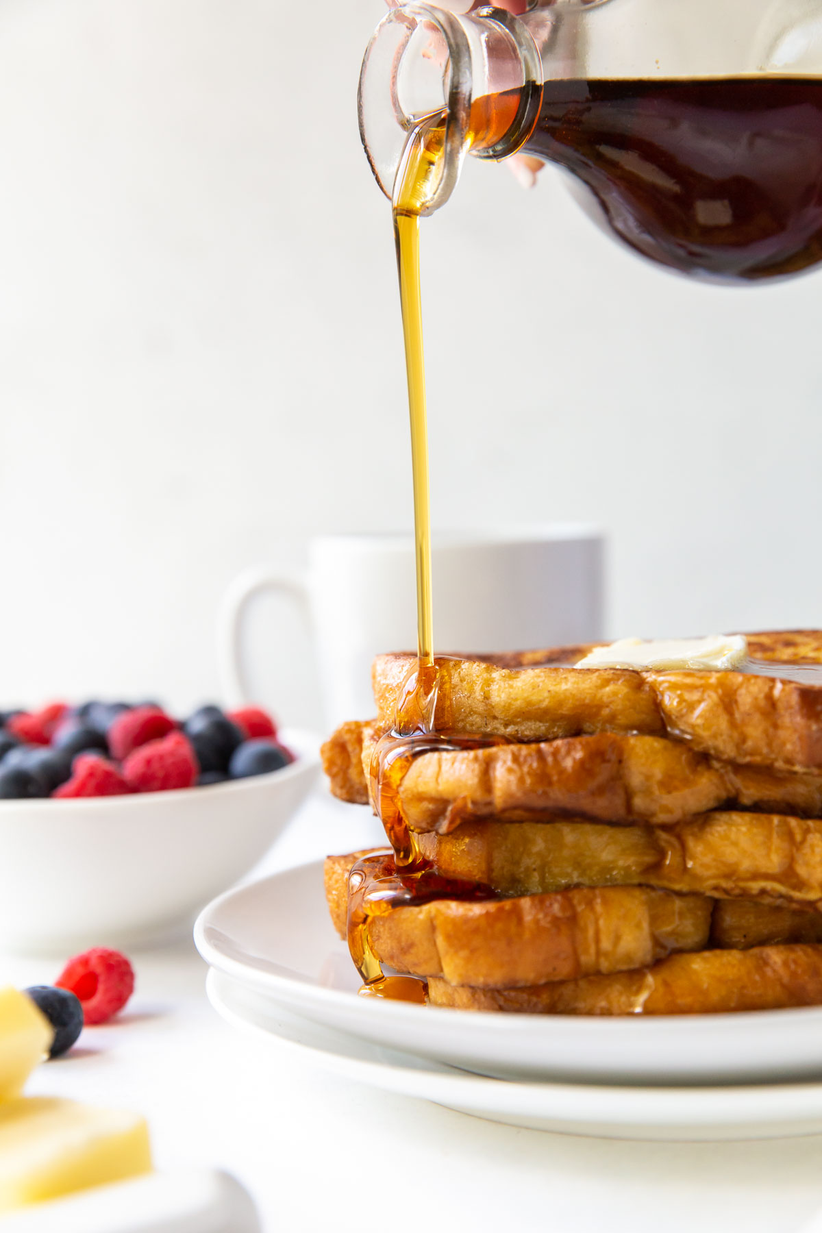 pouring maple syrup onto a stack of french toast