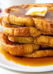 five slices of french toast stacked on a plate and topped with a pat of butter and maple syrup