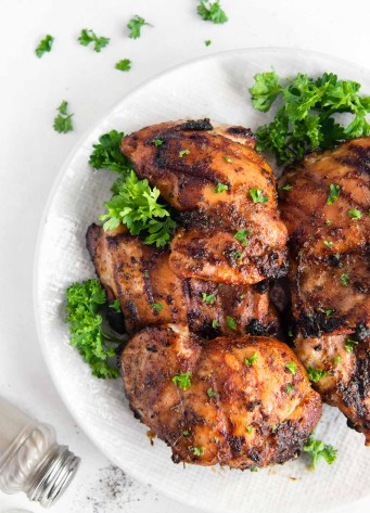 grilled boneless chicken thighs stacked on a plate with parsley garnish