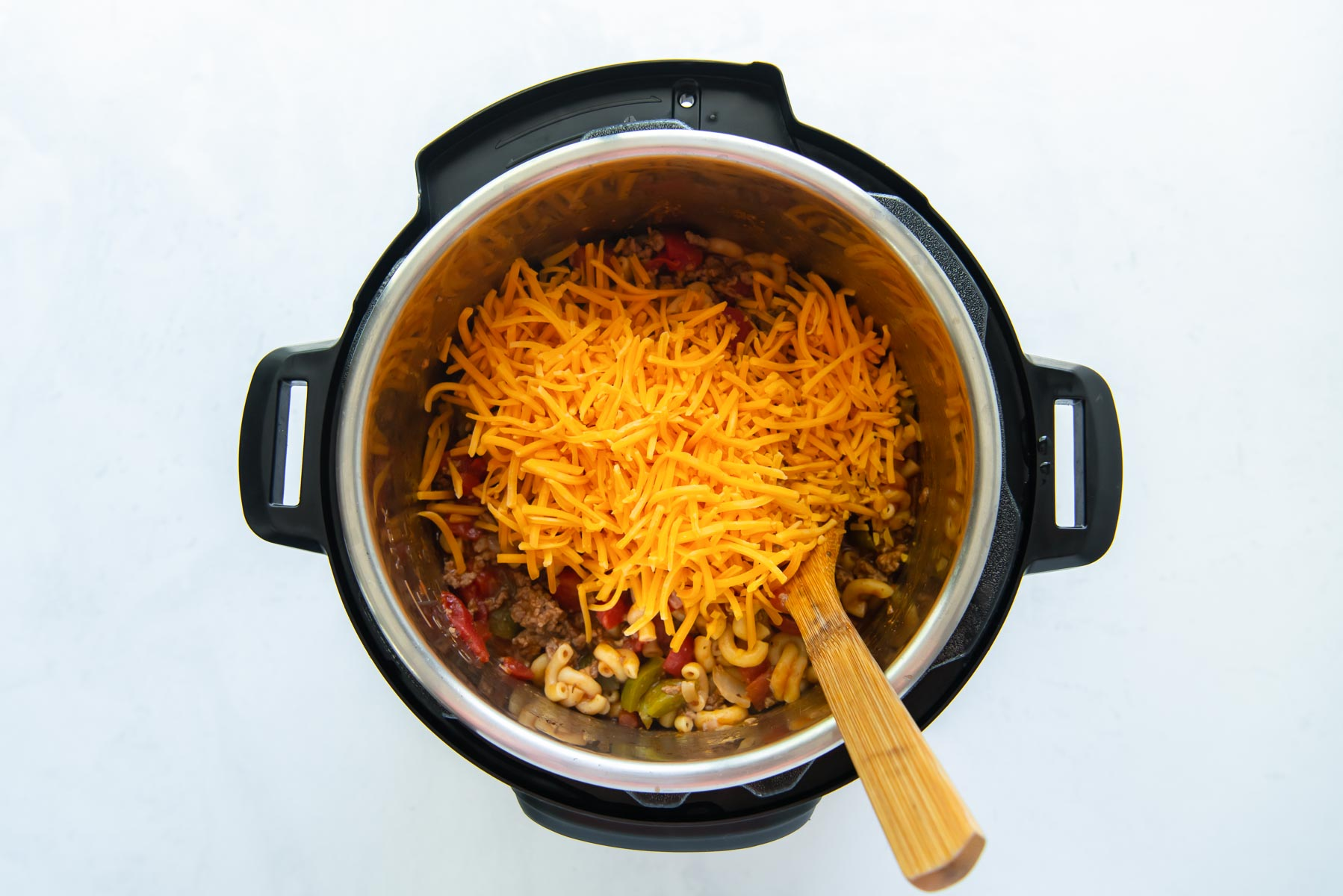 shredded cheddar cheese added to pot