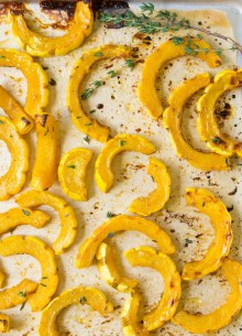 roasted delicata squash slices with thyme on a baking sheet