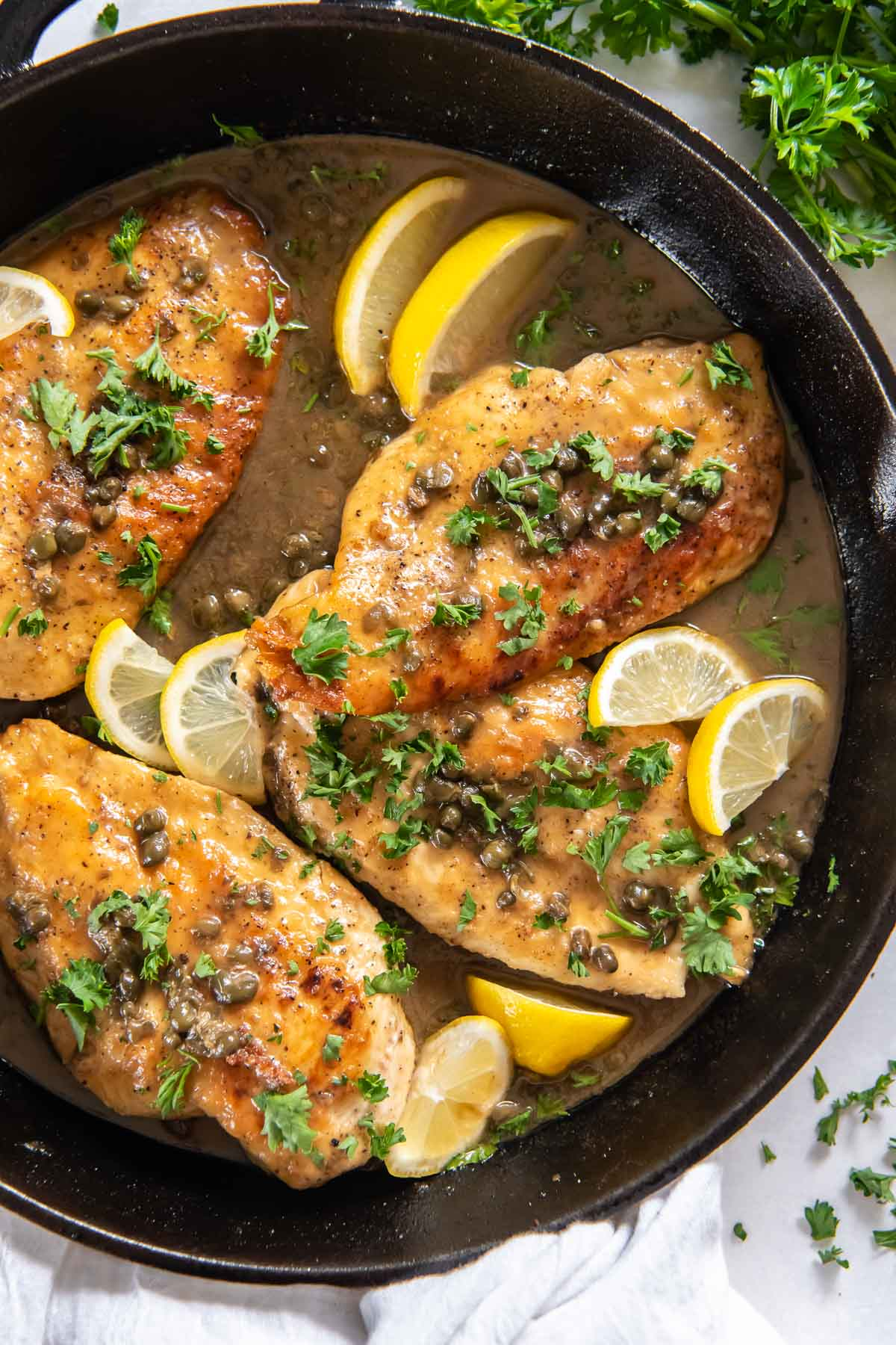 chicken piccata with fresh parsley and lemon slices in a cast iron skillet