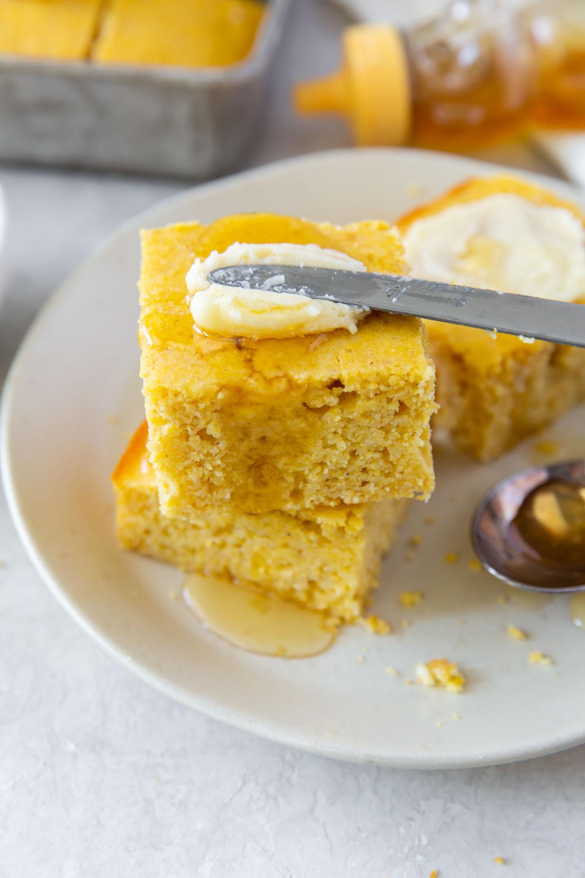 spreading honey butter on a piece of cornbread