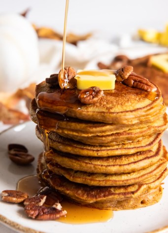 pouring syrup onto a stack of eight pumpkin pancakes with a pat of butter and pecan halves