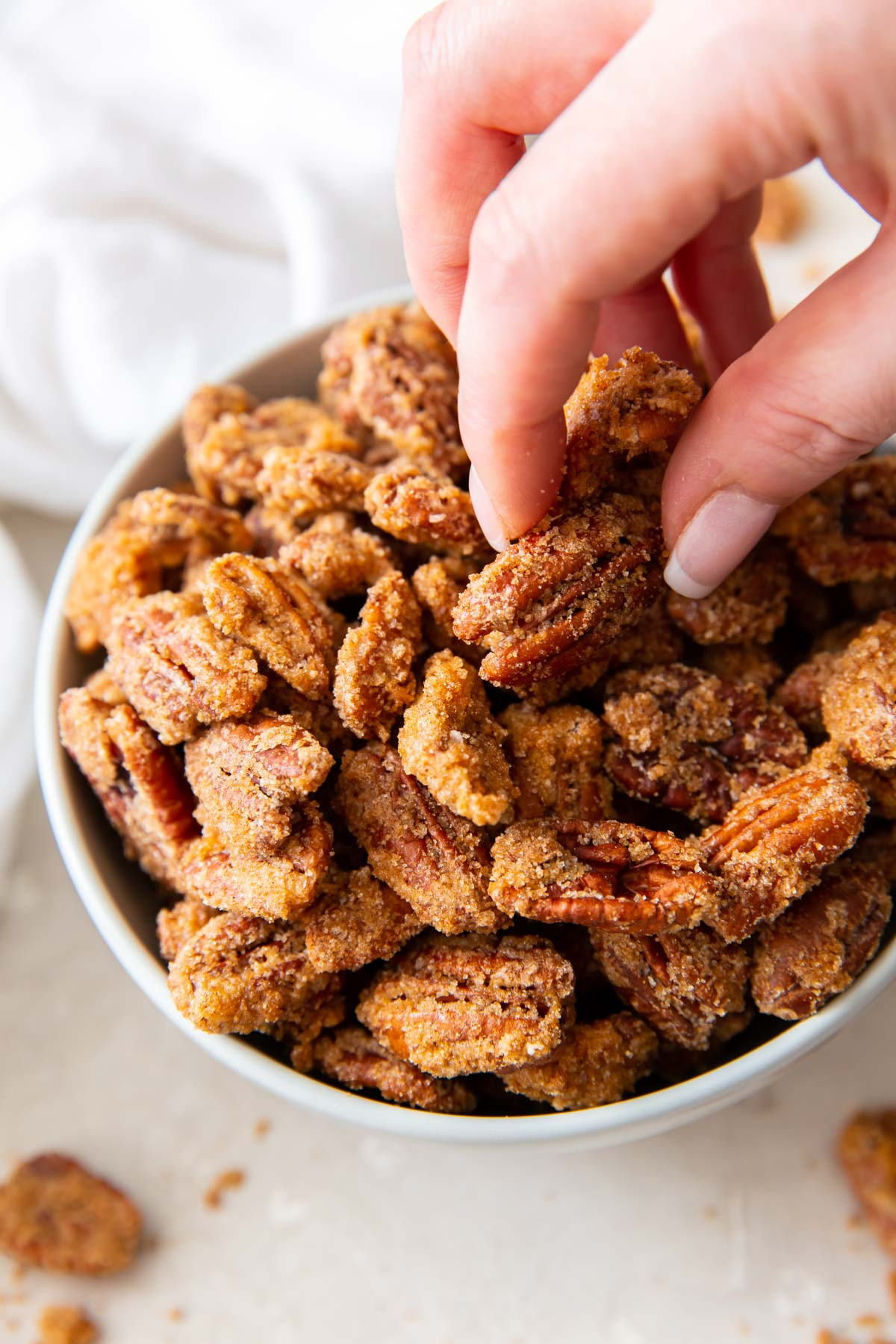 fingers grabbing a candied pecan out of a bowl