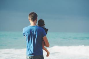 Father holding child, both are looking out to sea