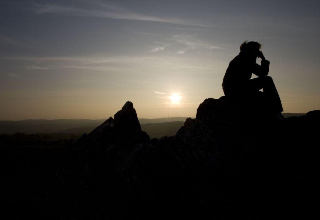 Man contemplating near sunset