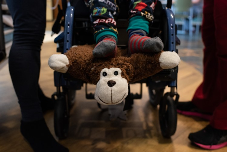 A child in a wheelchair rests his feet on a monkey stuffed animal.