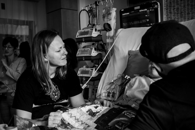 Heart mom Kristy Wolfe standing over her son's bedside at the Stollery Children's Hospital. Photo by Slice of Love Photography