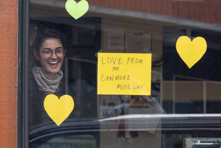 "A woman looks out a window with a sign that reads ""Love from the Canmore Museum"""