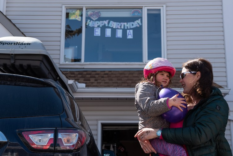A mother and daughter standing in front of a window with a birthday sign.