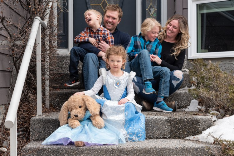 A young girl and her stuffed puppy wear princess dresses and pose for the camera while the rest of her family are having a tickle war in the background.