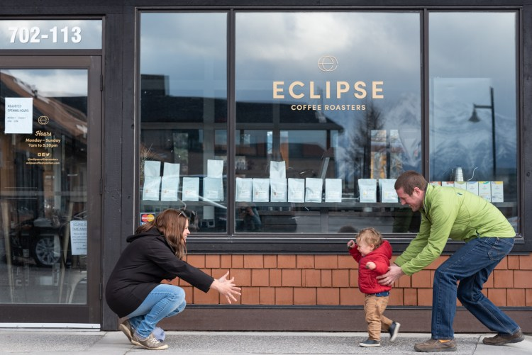 A toddler runs between his parents in front of Eclipse Coffee Roasters.