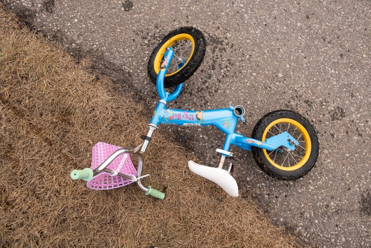A child's bike left on the side of a walkway.