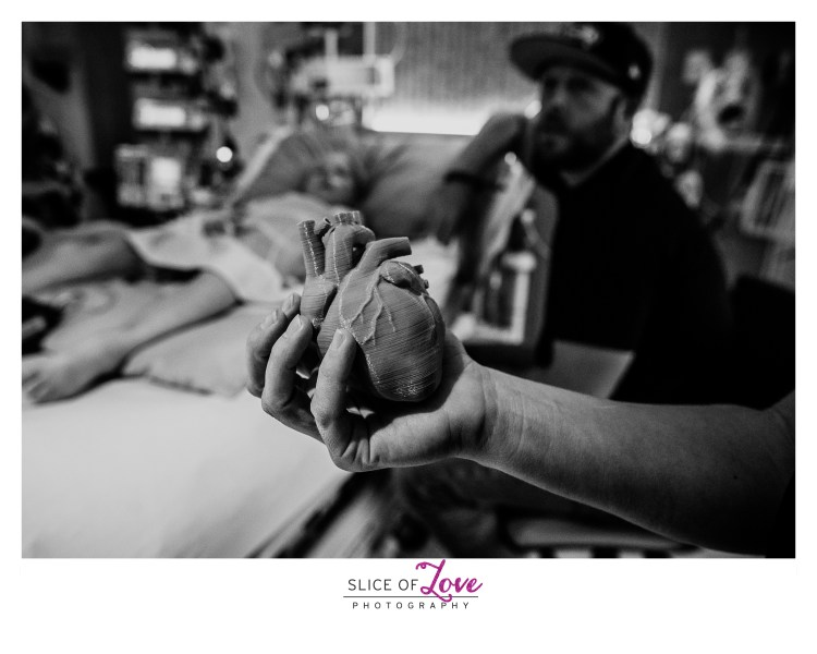 A 3D printed heart held in front of a heart warrior after surgery. Image by Slice of Love Photography
