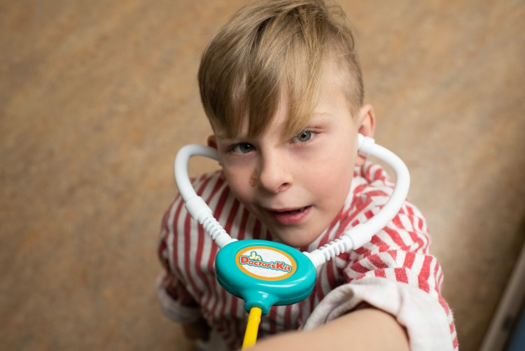 A young heart warrior uses a toy stethoscope during medical play. Image by Kristy Wolfe Photography