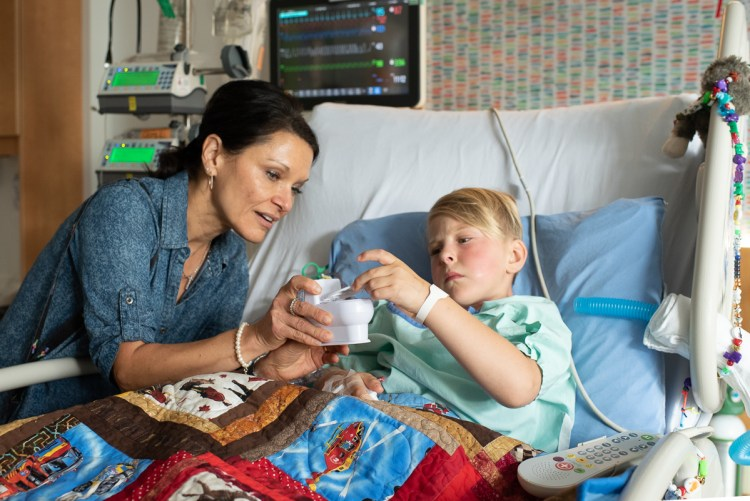 A Child Life Specialist supports a child in the cardiac intensive care unit.