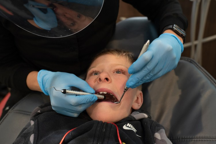 A young boy has his teeth checked by a pediatric dentist.