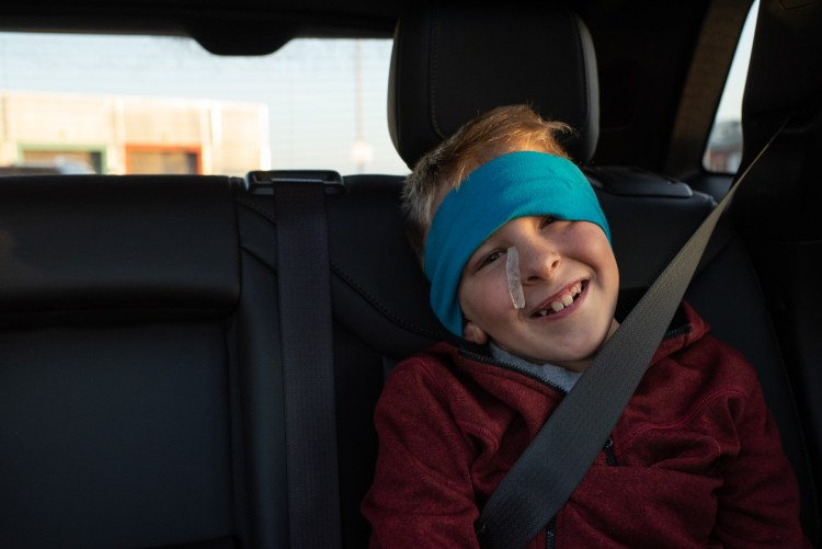 A smiling boy driving home after a hospital stay.