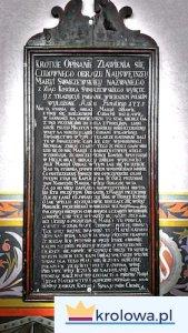 Drewniana tablica z historią figury.