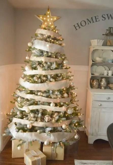 Her, fokuset på innredningen fra hvite og gyldne bånd, som sjenerøst omsluttet juletreet i en sirkel