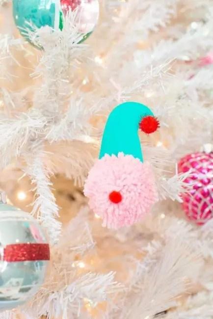 Эльф и Санта из помпона – проще простого. Понадобиться большой помпон и несколько маленьких, картон, клей. Из картона вырезают импровизированный колпак, соединяют все детали и украшение готового