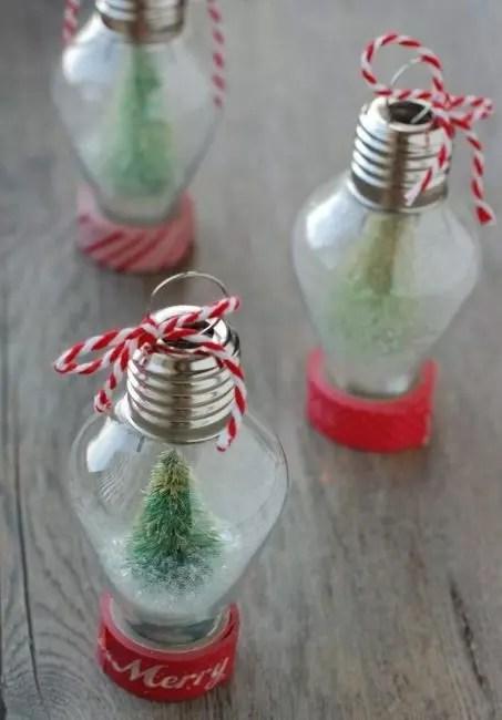 Старые лампочки – отличная основа для елочной игрушки. Для ее изготовления понадобится глиттер, искусственные еловые веточки, красная лента и шпагат