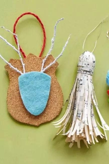 Подвеска из нотной бумаги оригинальное рождественское украшение. Для ее изготовления понадобится винная пробка как основа, нарезанная тонкими полосками нотная бумага, лента или прочная нитка. Бумагой оборачивают пробку, загибают края с помощью ножниц, фиксируют клеем для прочности