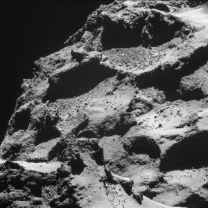 View from the smaller of Comet 67P two lobes (foreground in lower left) over to the larger lobe, which occupies most of the frame and which is dominated by rubble-filled depressions. One, just to the right of centre in the lower part of the image, has a near-circular appearance. It is expected that some circular pits on the comet are associated with the source of activity, perhaps as gas vents from the comet's porous interior. Whether this is such a feature is yet to be confirmed. NAVCAM image captured from a distance of 9.7 km from the centre of the comet. Image courtesy of European Space Agency - ESA.