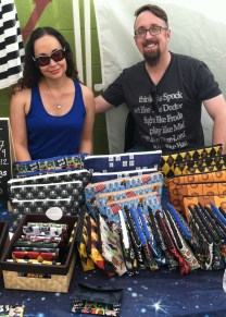 Wendy & Jason of Wyndmill Designs, showing off their eclectic selection of handmade accessories in a variety of fannish prints.