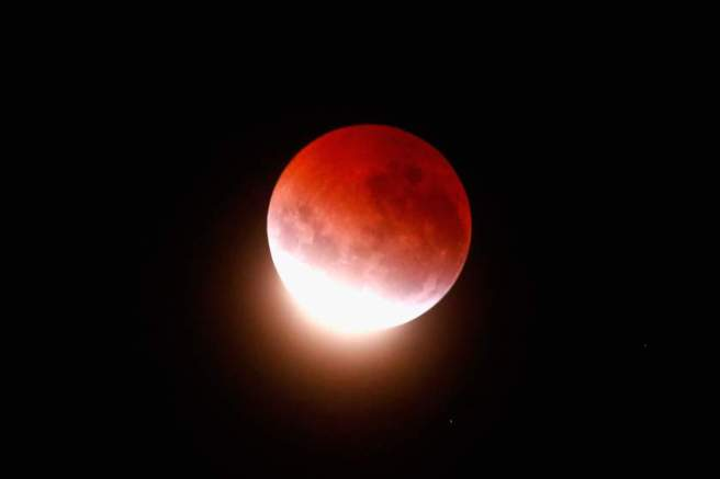 """AUCKLAND, NEW ZEALAND - APRIL 04: A blood red moon lights up the sky during a total lunar eclipse on April 4, 2015 in Auckland, New Zealand. The shortest total lunar eclipse, or """"blood moon"""", of the century will last just a few minutes. (Photo by Phil Walter/Getty Images)"""