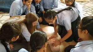 Schulsanitäterin zeigt, wie man den Kopf bei der Beatmung richtig überstreckt