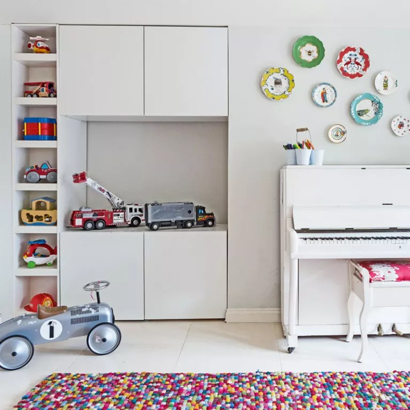 White living room with piano toys and storage in one corner