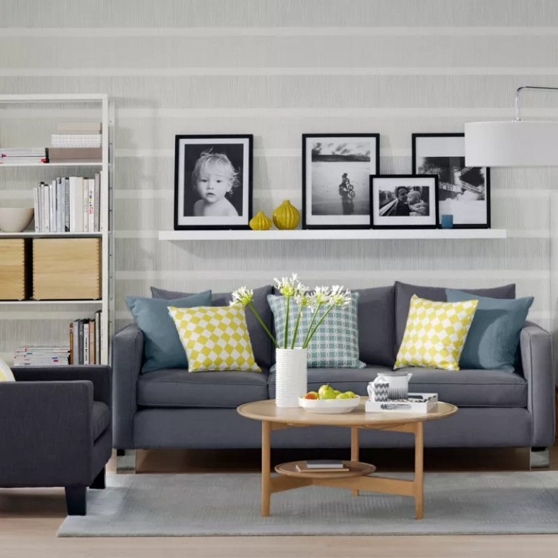 Living room with grey stripe wallpaper grey sofa and white storage unit