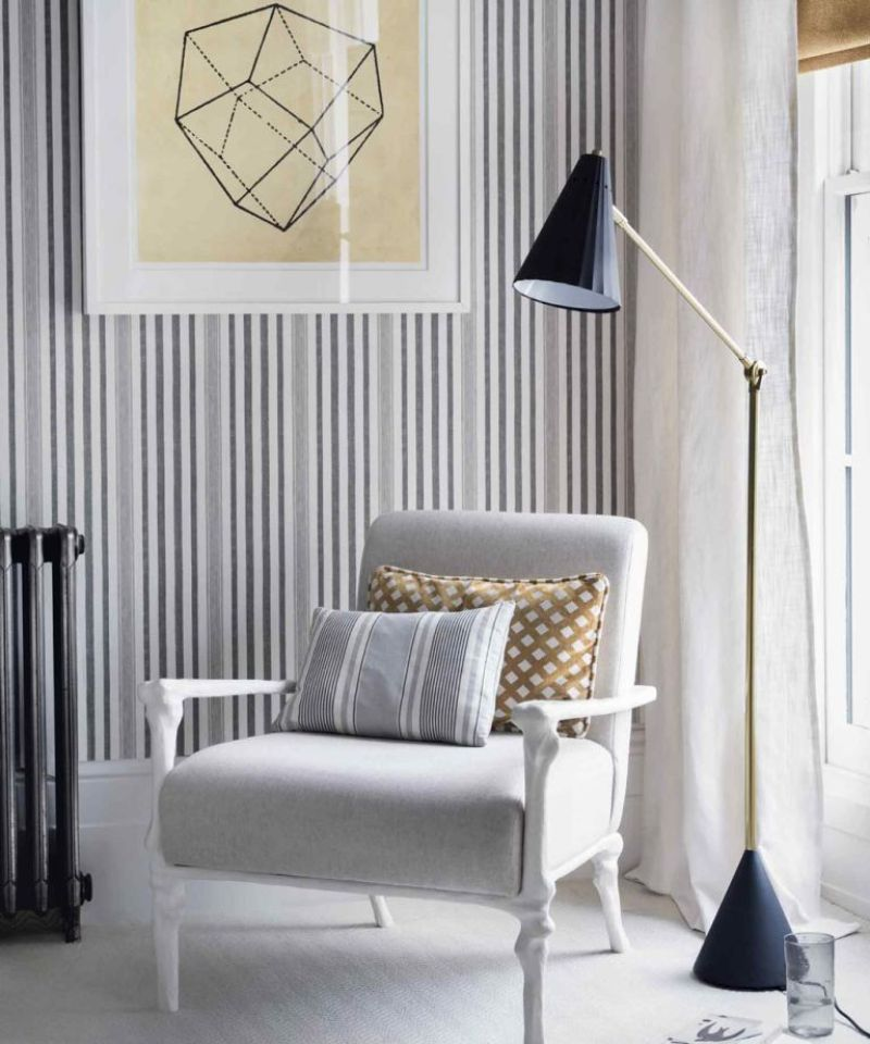 Pin striped wallpaper behind armchair in corner of a living room with black floor lamp