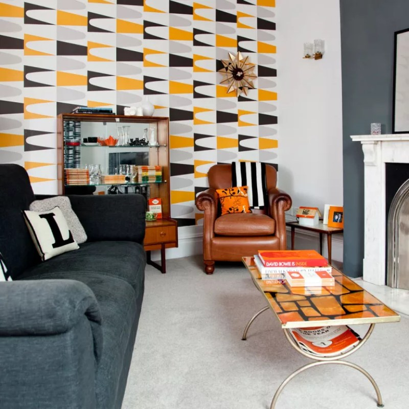 grey living room with retro geometric print wallpaper on one wall
