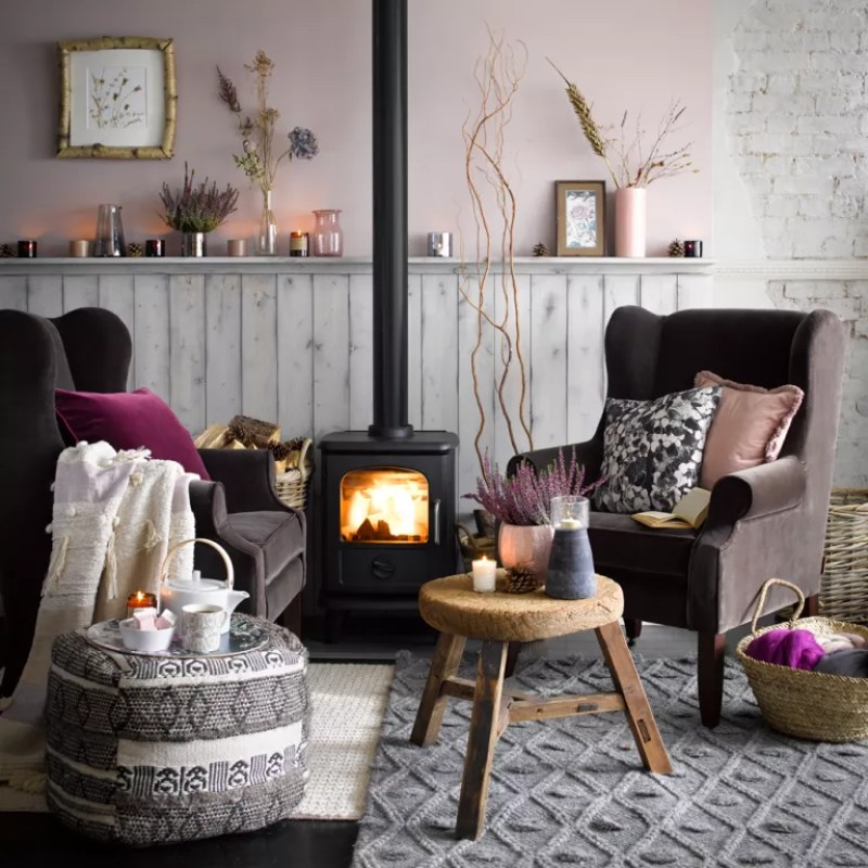 pale pink living room with brown armchairs either side of a log burner