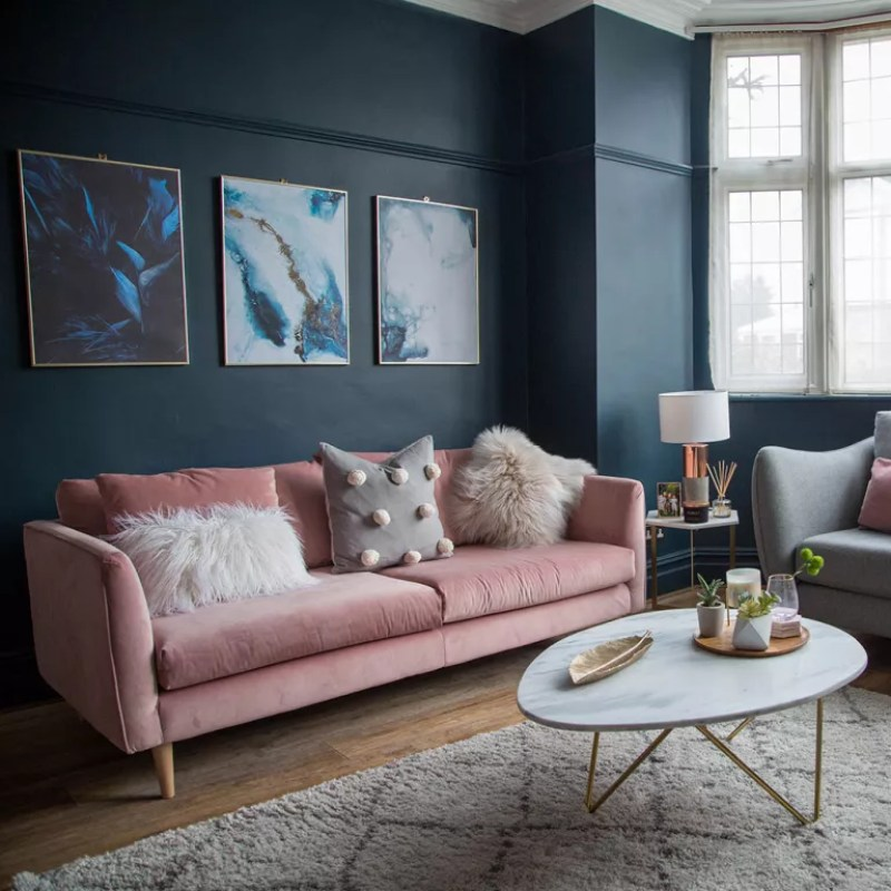 Living room with dark blue walls pink sofa and gold accessories