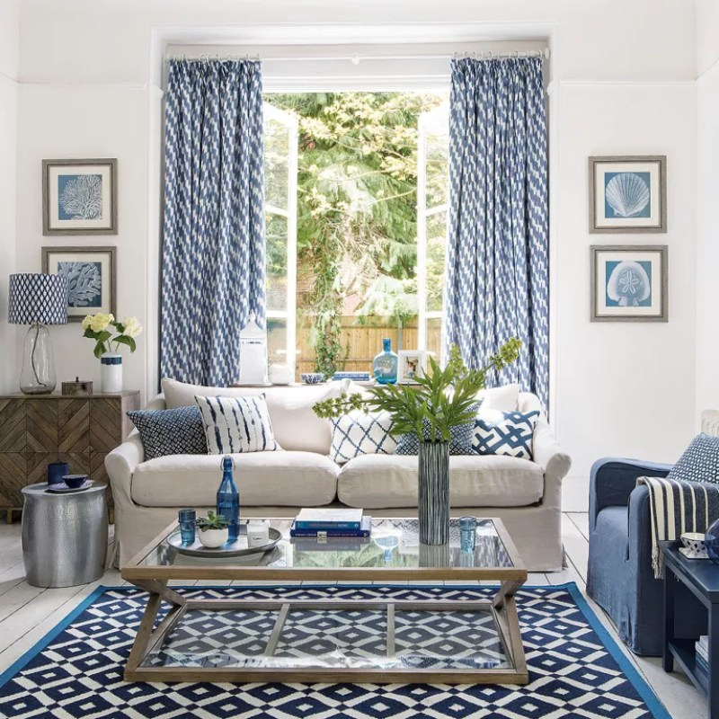Blue and white living room with patterned curtains and rug
