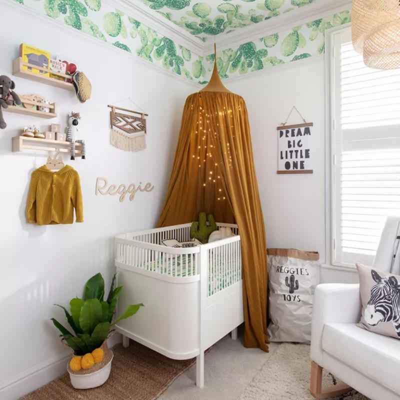 White nursery with cactus print wallpapered ceiling
