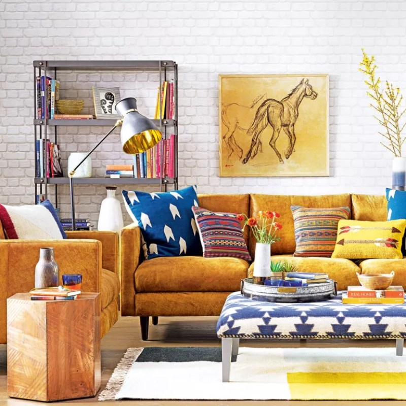 White living room with tan sofa and colourful cushions
