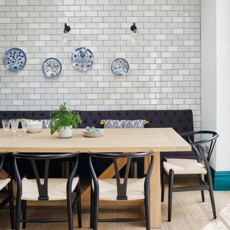 a dining table in a dining room with metro tile wall and plates as decor