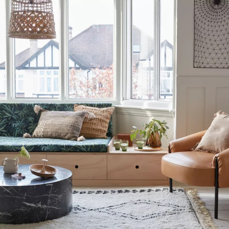 neutral living room with wooden window seat in bay window